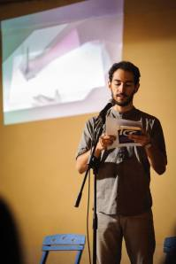 Marco Inguscio recites his prose poems, as Azzurra Cecchini illustrates his words in the background. Photo © Dino Maglie