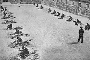 Prisoners crushing stone at the Robben Island B-Section courtyard. (UWC-Robben Island Mayibuye Archives)